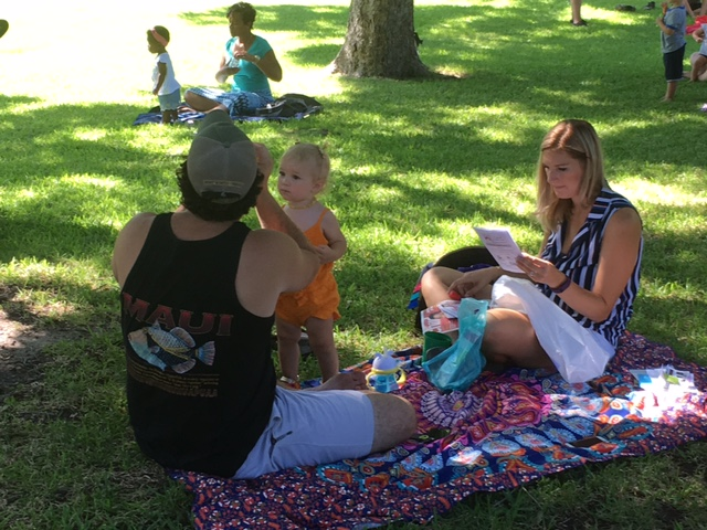 A family sits outside on a picnic blanket