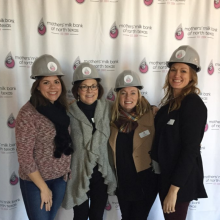 Four women in hard hats in front of logo step and repeat screen