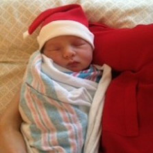 Newborn baby wearing Santa hat
