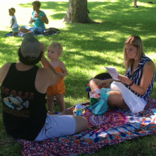 Mom, dad, and toddler on a picnic blanket