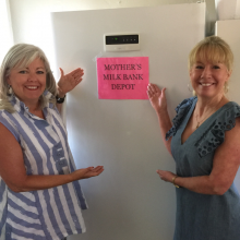 Two women standing on either side of an upright freezer