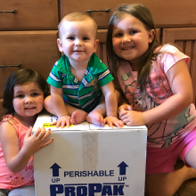 Young girl, toddler girl and baby boy sitting around a box