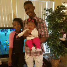 Older brother holding baby sister, middle sister standing next to them