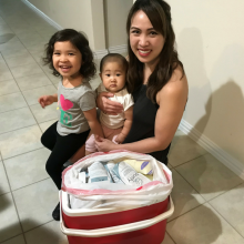 Mother, baby and toddler next to a cooler full of frozen breastmilk