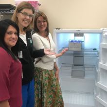 Three women standing next to an open upright freezer