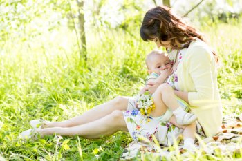 Mother breastfeeding baby outdoors
