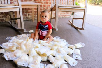 Baby sitting among frozen milk bags