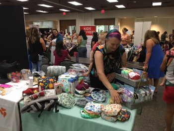 Woman with baby peruses baby items for sale.