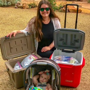Mother and baby posed next to two coolers of breastmilk